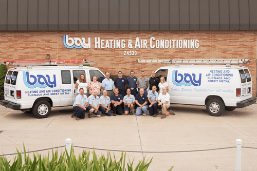 Bay Heating & Air Conditioning employees standing next to their vans.